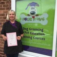 Renea shows of her completion certificate ourtide Four Paws Groom School